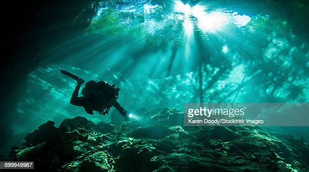 Diver passes through light beams in Chac Mool cenote in Mexico.
