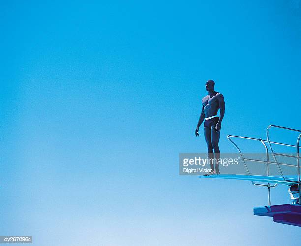 diver perched on edge of diving board - black men in speedos stock photos and pictures