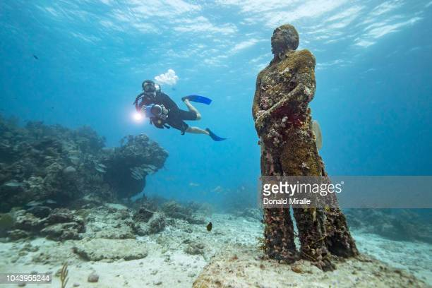 A diver photographs a massive statue of a man at MUSA off the coast of Isla Mujeres Mexico on September 26 2018 Consisting of over 500 permanent...