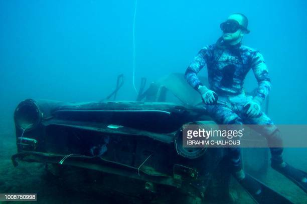 TOPSHOT A diver poses for a photograph next to an immersed car off the coast of the southern Lebanese port city of Sidon on August 1 2018...