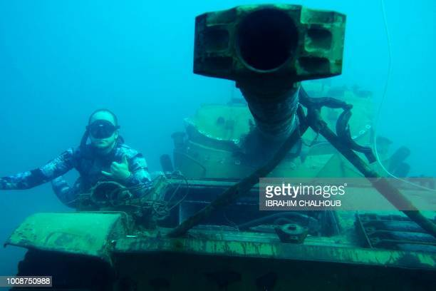 A diver poses for a photograph next to an immersed tank off the coast of the southern Lebanese port city of Sidon on August 1 2018 Environmental...