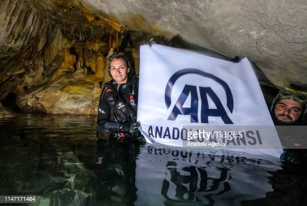 A diver poses with the amblem of Anadolu agency at underwater cave similar with fairy chimneys which is under inactive Volcanic Mount Kel at Yayladag...
