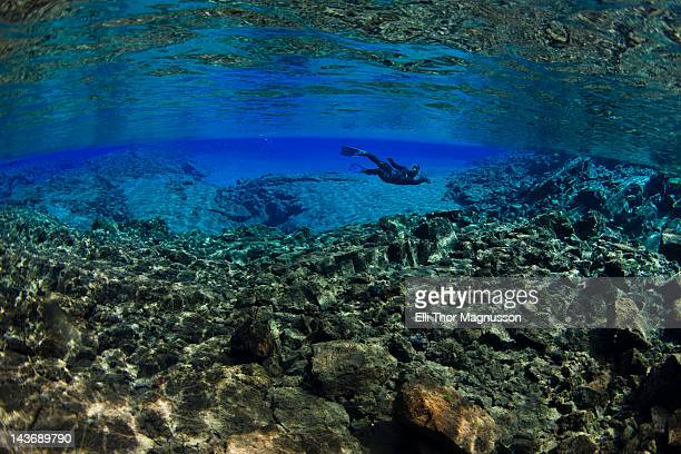 diver swimming by rock formations - thingvellir stock photos and pictures