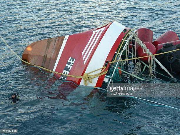 """Diver swims next to the remains of the ship """"Siempre Cansina"""" at the coast of Vivero, northwestern Spain, 24 February 2005. The bodies of four dead..."""