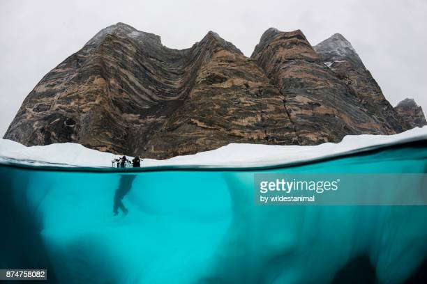 Diver taking a selfie while standing on an iceberg in Scoresbysund Fjord, eastern Greenland.