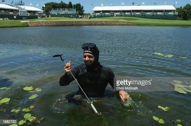 Diver Terry McAvoy comes out from the water after retrieving John Daly's putter and ball from the 18th hole lake during round three of the Australian...