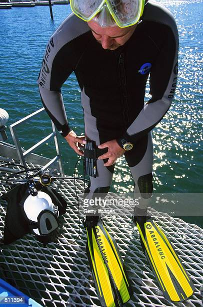 A diver tries on an electronic shark repellent unit in this undated photo The antishark device sends an electronic field affecting the sharks''...