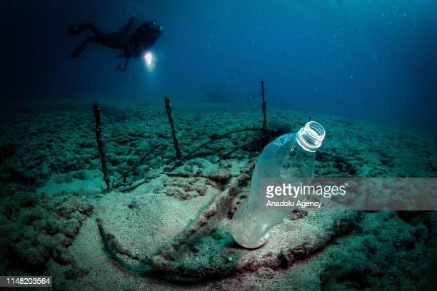A diver with a flashlight descends into the water and flash a plastic bottle up at the Samandag diving site off the coasts of Samandag near the...