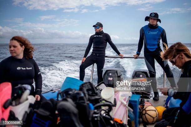 Divers are seen in an inflatable boat as they sail for a baited shark dive in Umkomaas near Durban, South Africa, on December 10, 2020. - Aliwal...
