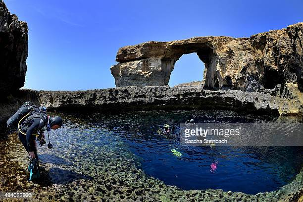 Divers are seen in front of the natural arch 'The Azure Window' at Dwejra Bay on May 20 2014 in Dwejra/Gozo Malta