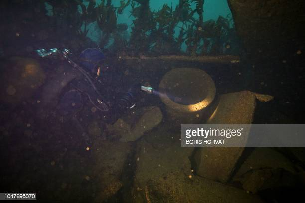 Divers go inside the wreckage of the super tanker AmocoCadiz at 25 meters of depth off the coast of Portsall northwestern France on October 5 2018...