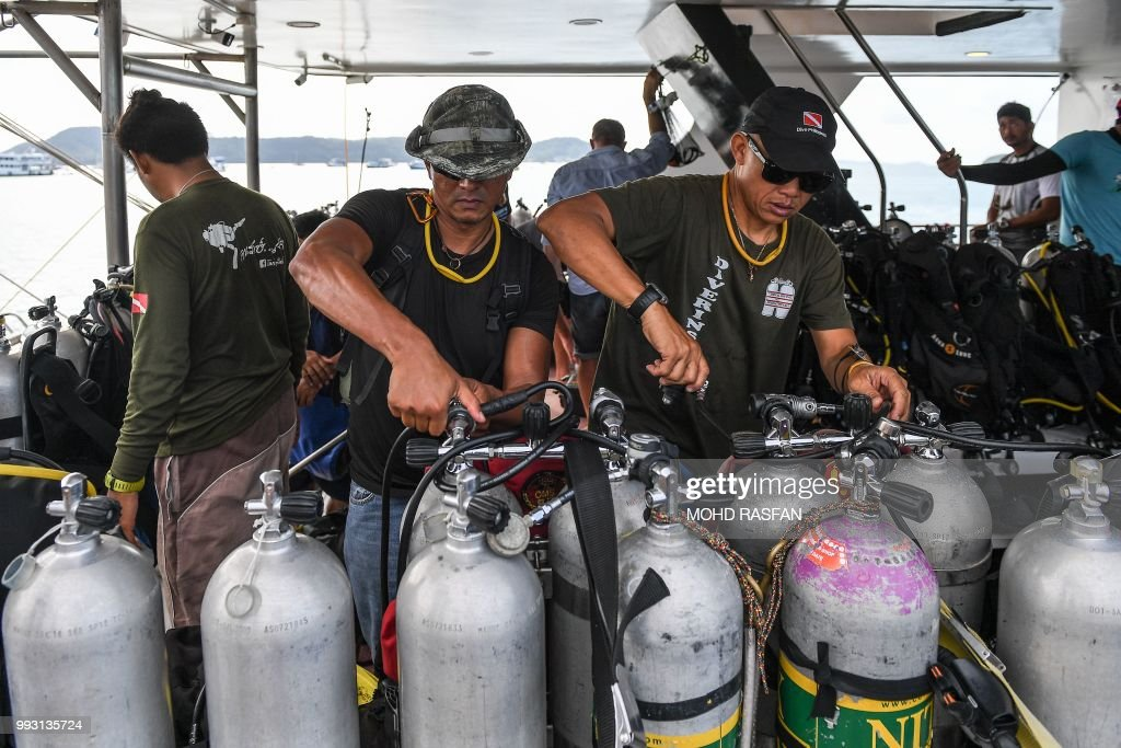 Divers inspect oxygen tanks at Chalong pier in Phuket on July 7, 2018, as rescue operations continue for missing tourists following a boat accident on July 5. - Thai rescuers pulled 37 bodies from waters off the coast of the holiday island of Phuket on July 6 after a tourist boat went down in heavy seas with dozens of Chinese passengers on board.
