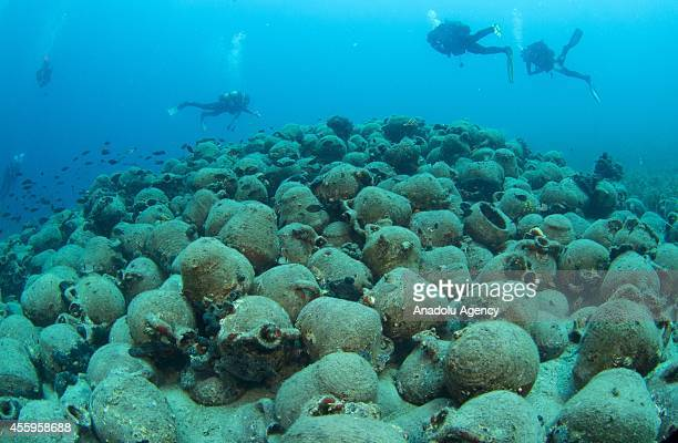 Divers inspect the 1000 years old amphora stack during their diving session in the Aegean Sea near the Maden Island of Balikesir Turkey on September...