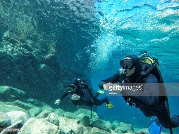 divers jumping from the boat in water - gas tank stock photos and pictures