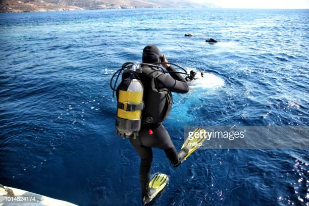 taucher aus dem boot ins wasser springen - sporttauchen stock-fotos und bilder