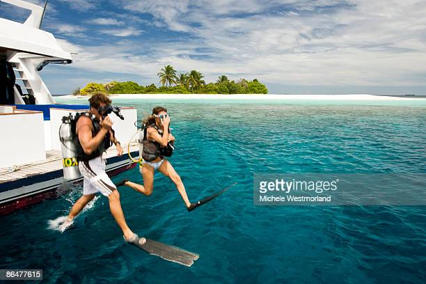 divers jumping into ocean, maldives - maldives stock pictures, royalty-free photos & images