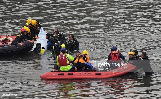 Divers lift two bodies of victims from the Transasia ATR 72600 turboprop plane crash onto boats in the Keelung river in New Taipei City on February 6...