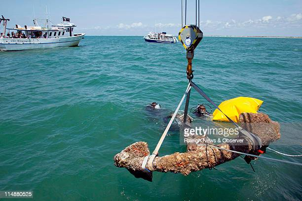 Divers maneuver a 3000 pound anchor recovered from the shipwreck of Blackbeard's Queen Anne's Revenge closer to the Research Vessel Dan Moore which...