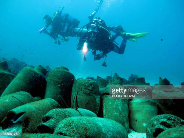 Divers observe Roman ancient amphoras down onto sand on December 4 2011 off the coast of the Frioul island southern France Discovered in 1952 by...