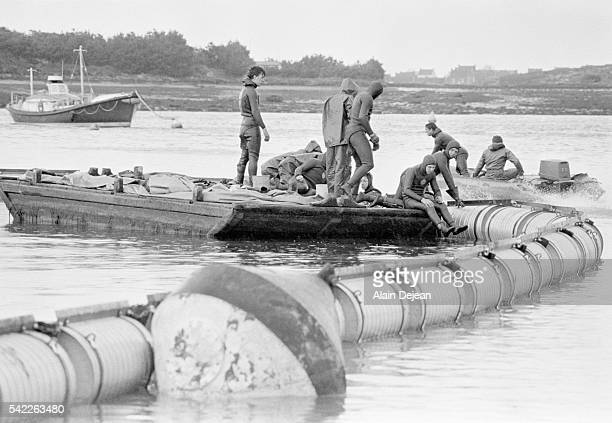 Divers of the French Navy set up water boom made of metal blocks to slow the movement of oil spread by high winds after the Amoco Cadiz disaster The...