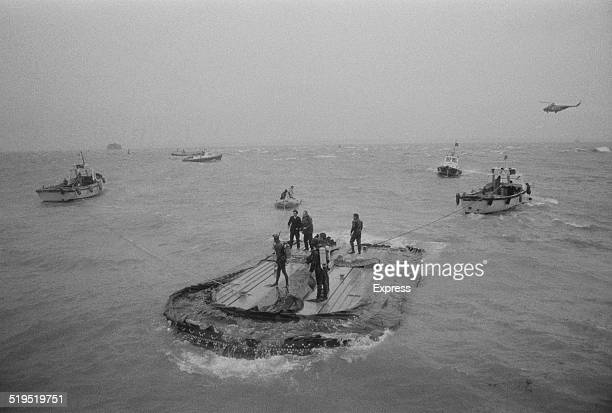 Divers on the upturned hull of hovercraft SR-N6 012 after an unsuccessful attempt to cut a hole in the hull to reach survivors after a freak wave...
