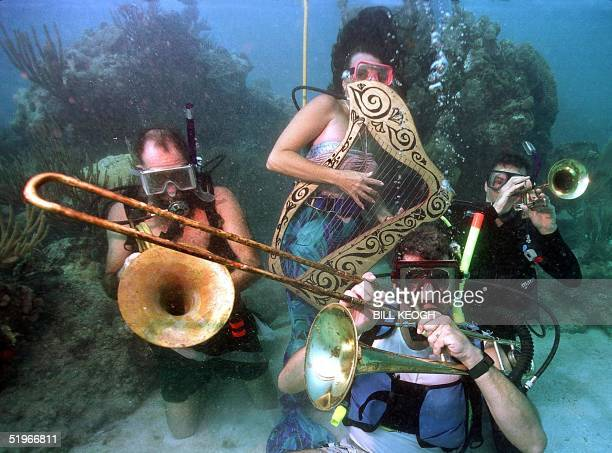 Divers participating in the Lower Keys Underwater Music Festival pretend to play musical instruments underwater 08 July 2000 off the Florida Keys The...