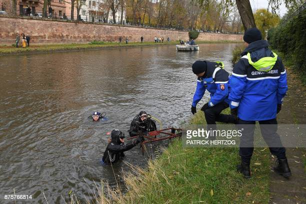 Divers pull a roadwork fence out of the Ill river helped by Gandarmes during a cleanup mission in Strasbourg eastern France on November 18 2017...