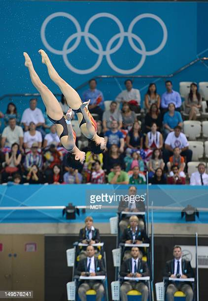 Divers Ruolin Chen and Hao Wang of China glide past the Olympic Rings and the judges during back dive in the second round of the women's synchronized...
