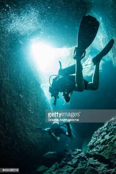 scuba divers swim inside underwater caver - スクーバダイビングの視点 ストックフォトと画像