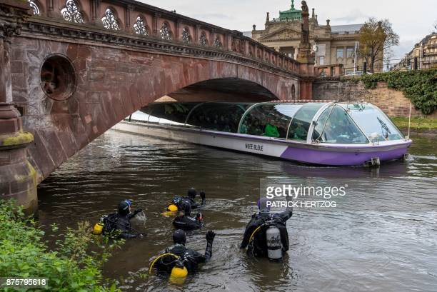TOPSHOT Divers wave at people in a tourist boat during a cleanup mission of the Ill river in Strasbourg eastern France on November 18 2017 Hundreds...