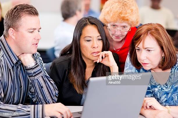 Diverse adult students working in a team on laptop