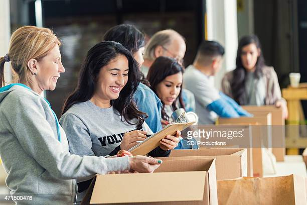 diverse adults packing donation boxes in charity food bank - charity and relief work stock pictures, royalty-free photos & images