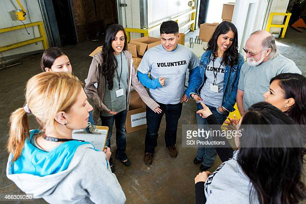 Diverse adults volunteering in food bank together