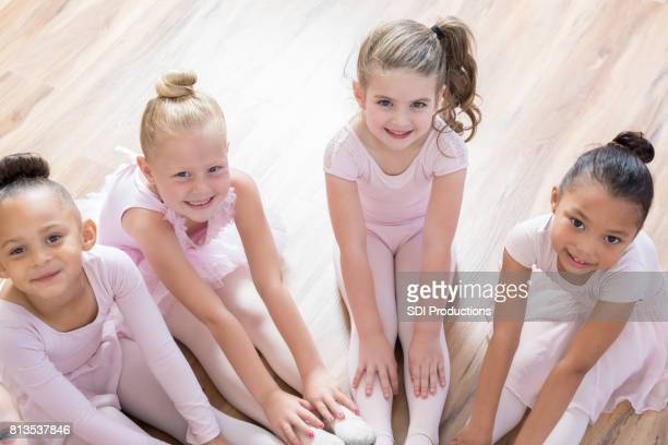 diverse ballet beauties sit in a circle together - little girls dressed up wearing pantyhose stock photos and pictures