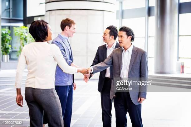 ejecutivos de negocios diversos saludo en su oficina de lobby - romper el hielo fotografías e imágenes de stock