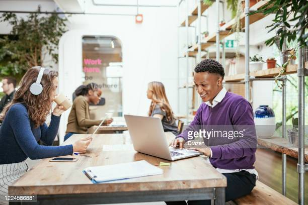 diverse business people telecommuting from cafe - employee stock pictures, royalty-free photos & images