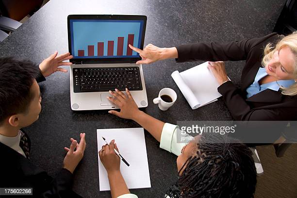 Diverse business team analyzing chart on a laptop