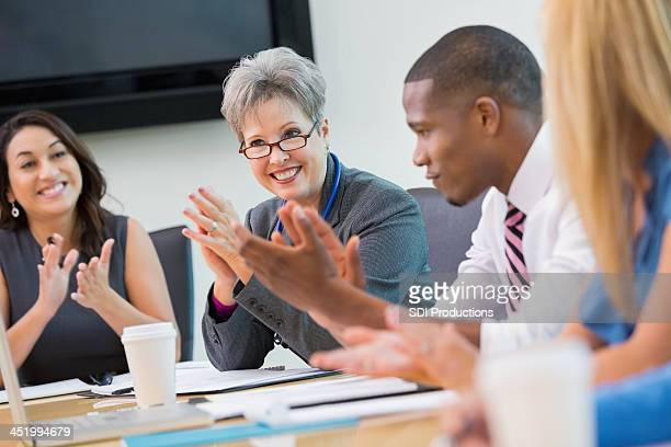 Diverse business team applauding during staff meeting