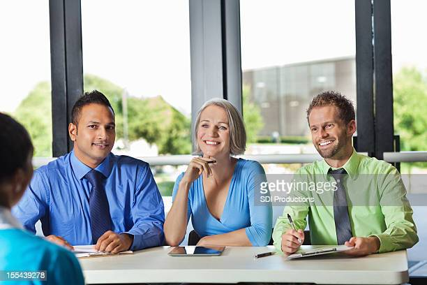 diverse business team conducting interview or review with prospective employee - job fair stock pictures, royalty-free photos & images