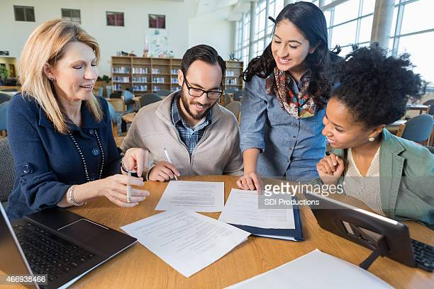 Diverse business team or study group working together in library