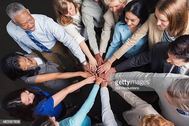 Diverse business team with hands in huddle to celebrate success