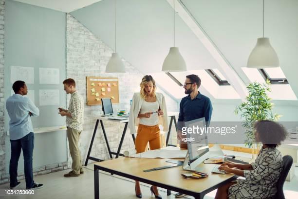 équipe de diverses entreprises travaillant au bureau - agence de design photos et images de collection