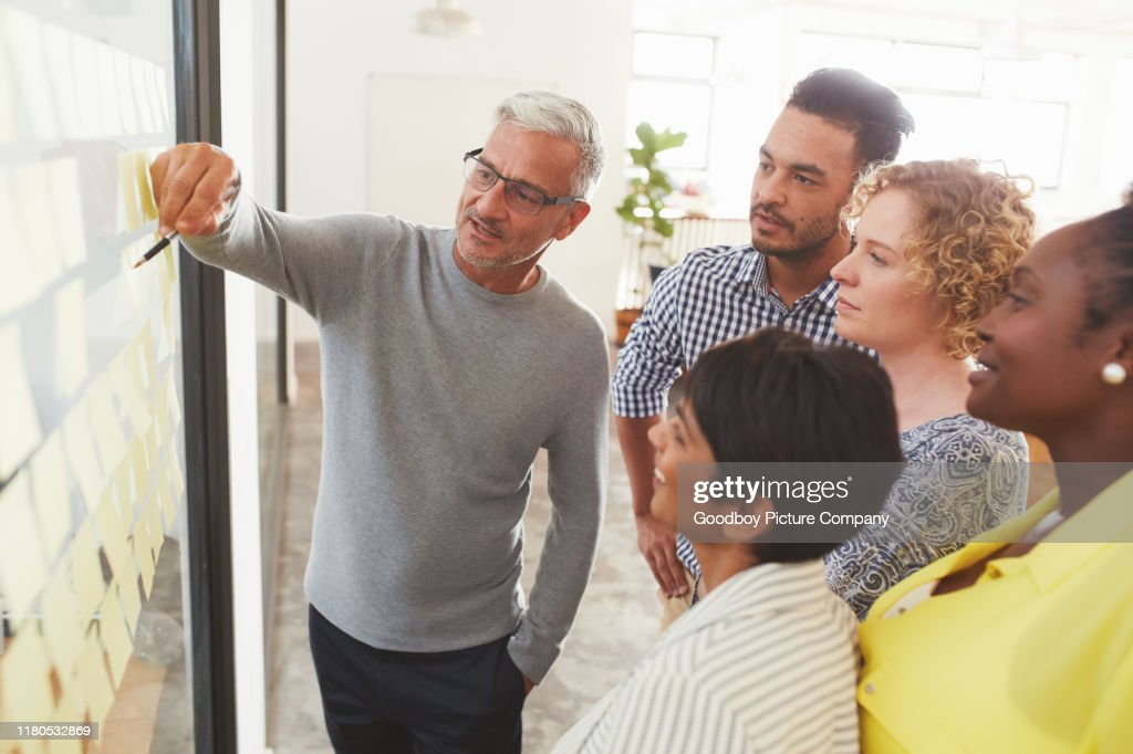 Diverse businesspeople brainstorming with adhesive notes in a meeting : Stock Photo