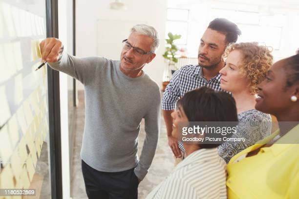 diverse businesspeople brainstorming with adhesive notes in a meeting - diagramma di flusso foto e immagini stock