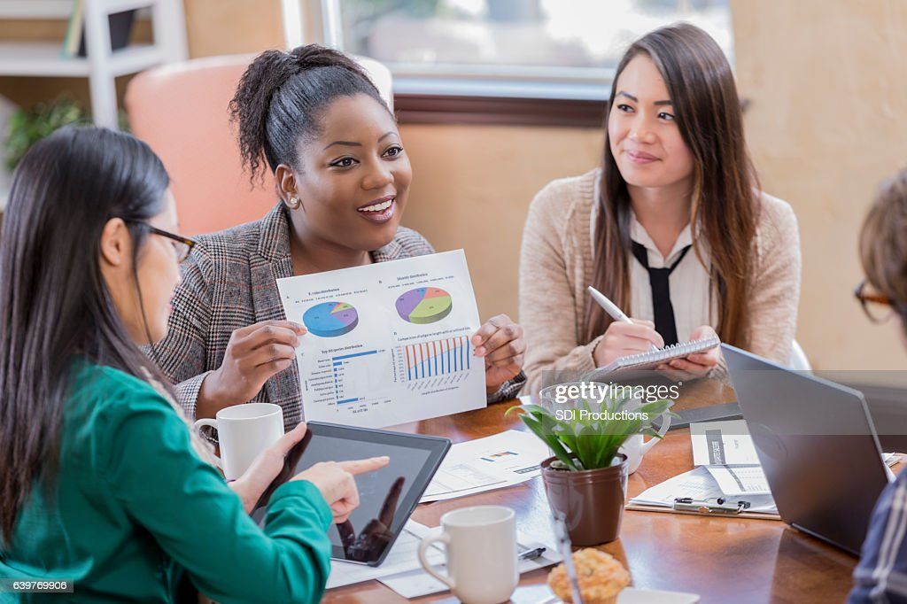 Diverse businesspeople discuss financials during meeting : Stock Photo