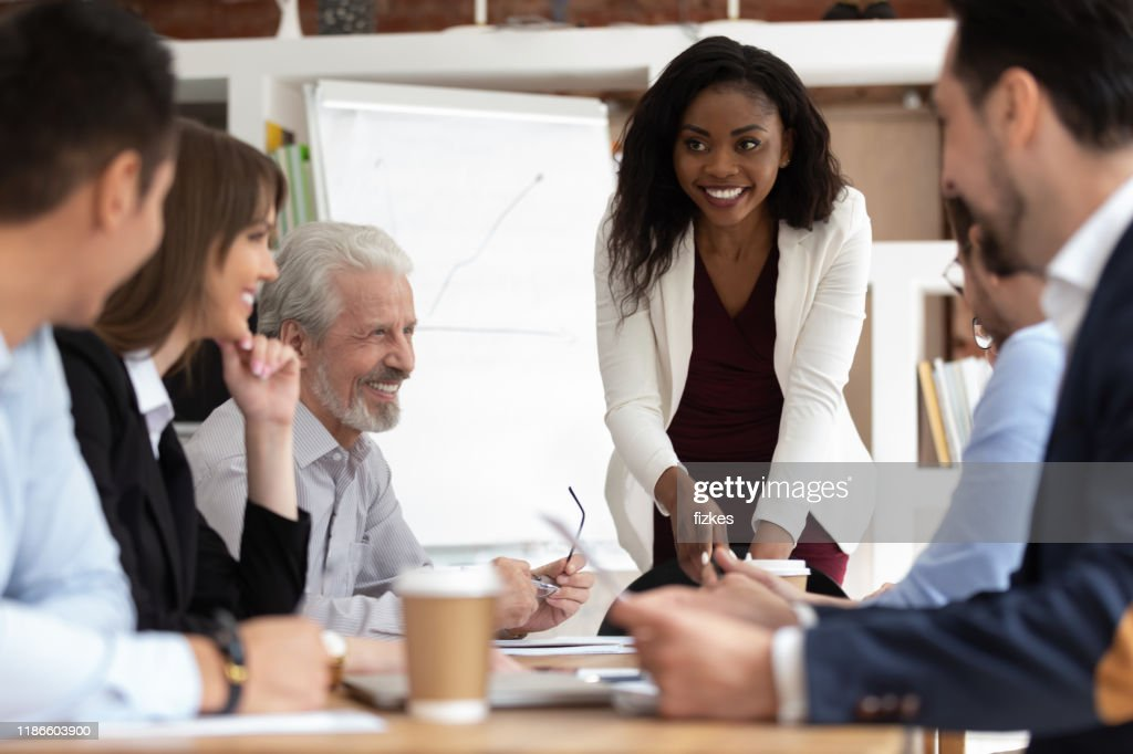 Diverse businesspeople gathered together for negotiations lead by african businesswoman : Stock Photo