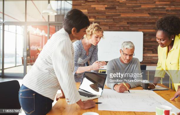 diverse businesspeople putting ideas to paper during a meeting - employee engagement stock pictures, royalty-free photos & images