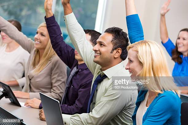 Diverse businesspeople raising hands during meeting or conference