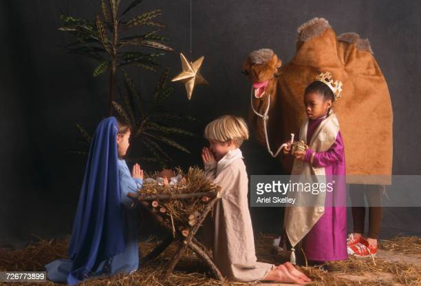 diverse children acting in nativity scene - manger stock photos and pictures