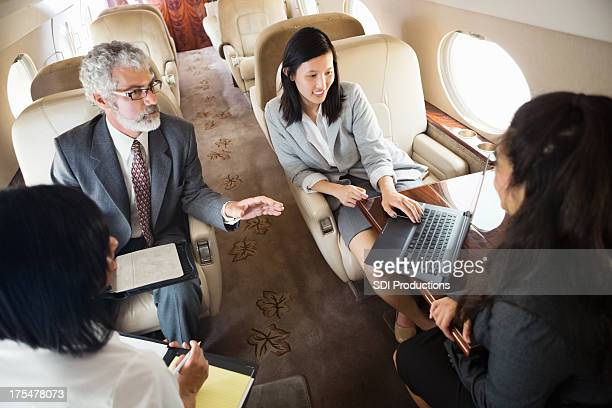 Diverse colleagues working whle travelling on company jet